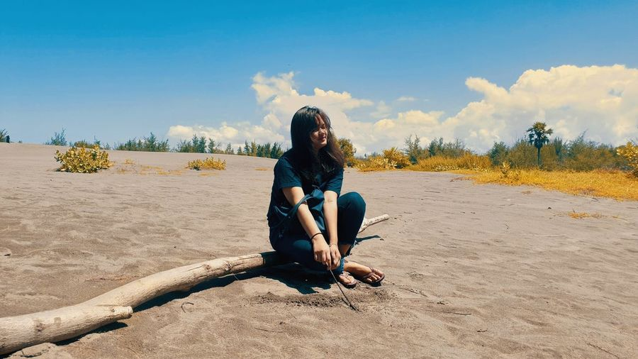 Young woman sitting on land against sky
