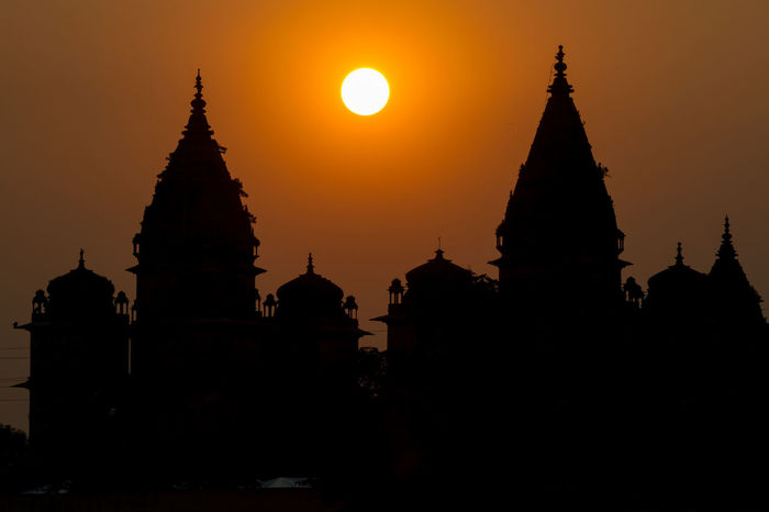 Silhouette of temple and cenotaphs at sunset by Betwa river, Orchha, India. Architecture Cultures India Orchha Outdoors Pagoda Place Of Worship Religion Silhouette Silhouette Sunset