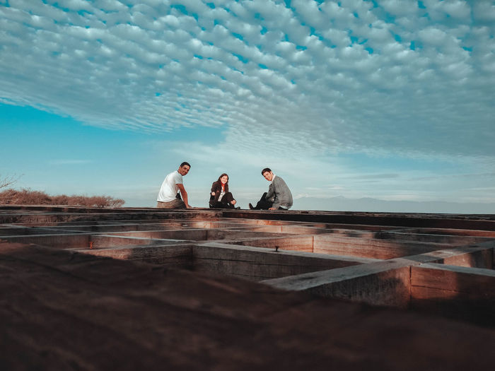 Friends sitting on wooden built structure against blue sky