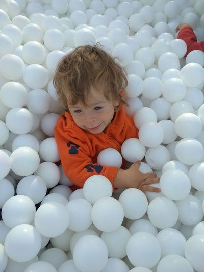 Cute boy sitting in ball pool