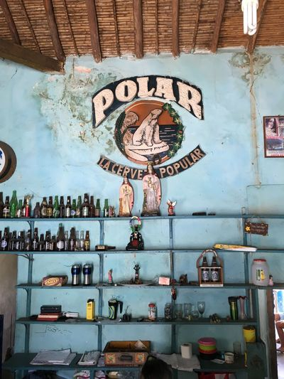 Multi Colored Day Indoors  No People Hanging Blue Wall Religious Images Bottles Collection Bottle Display Polar Beer Colonial Style Colonial Architecture Bodega Vintage Ceiling Blue Turquoise