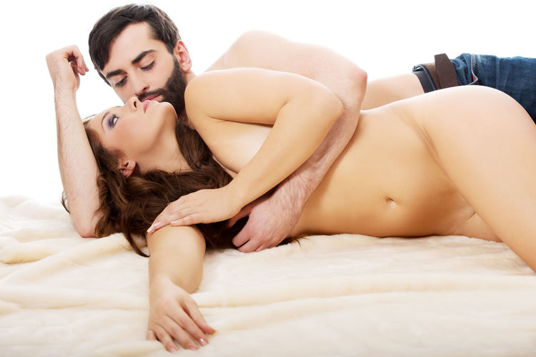 Couple romancing while lying on bed at home