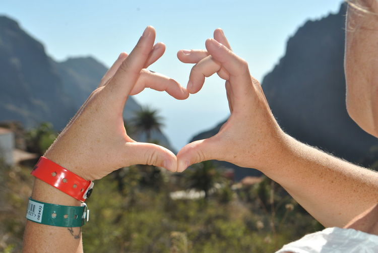 Cropped hands of man making heart shape against sky