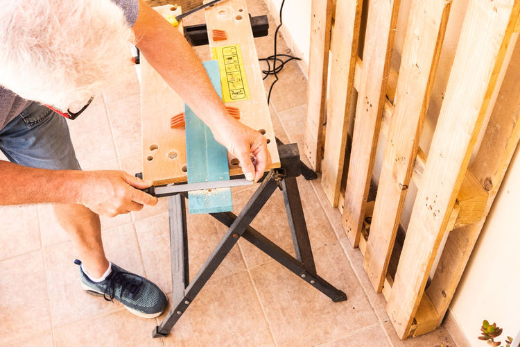 Corner of carpentry with a senior man working at wooden table recycling old wood from the pallets. Funny hobby for a retired people, with white hair and beard Accessory Activity Afternoon Background Beard Board Build Carpenter Carpentry Casual Caucasian Concept Construction Drill Engineer Furniture Glasses Hammer Hobby Holding Industrial Industry Instrument Interest Job Labor Lifestyle Man Manual Manufacturing Meter Object Pallelts People person Professional Recycled Renovation Screwdriver Senior Side View Site Studio Technology Tool White Hair Wood Woodworking Work Working