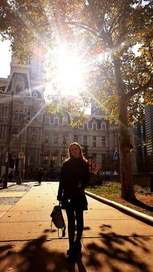 Silhouette of woman walking on street in city