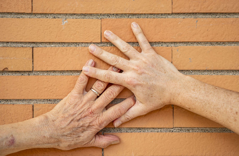 Cropped hands on wall