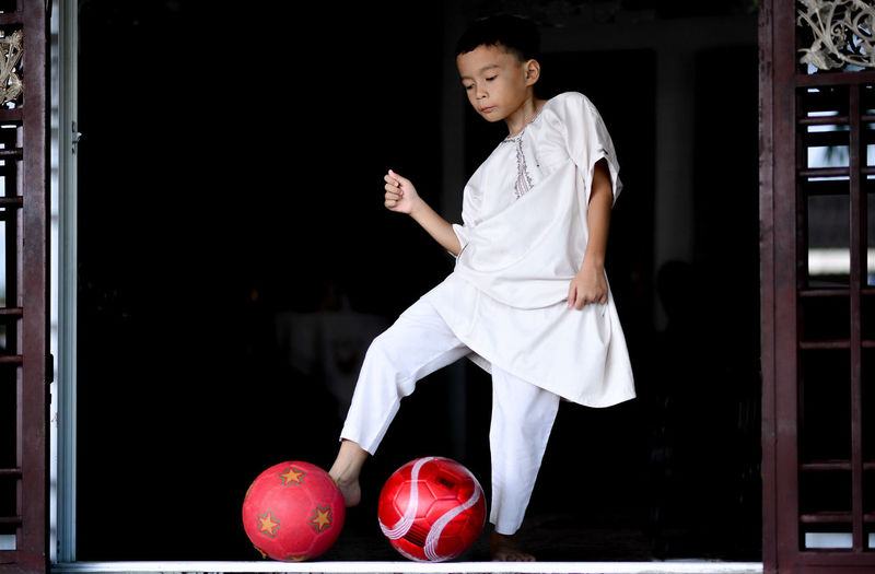 Low Angle View Of Boy Kicking Red Balls
