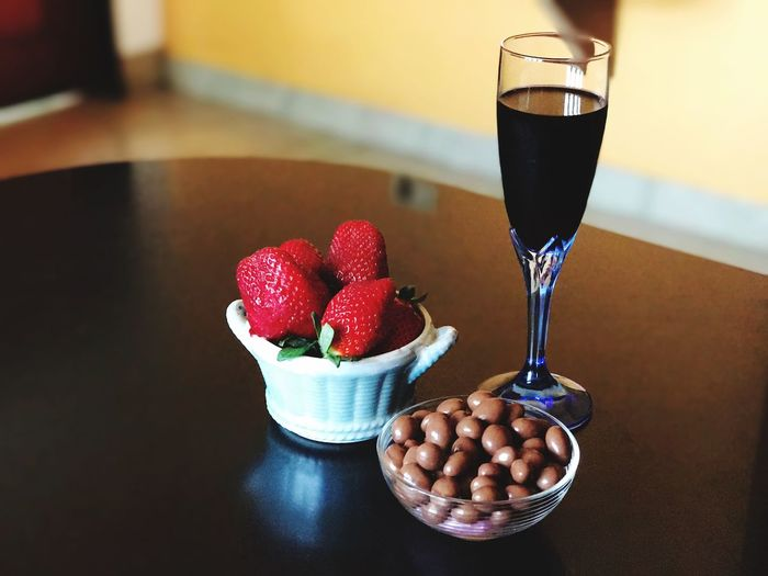 Close-up of strawberries with chocolates and drink on table