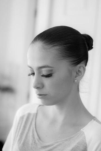 Close-up of young woman wearing false eyelash at home