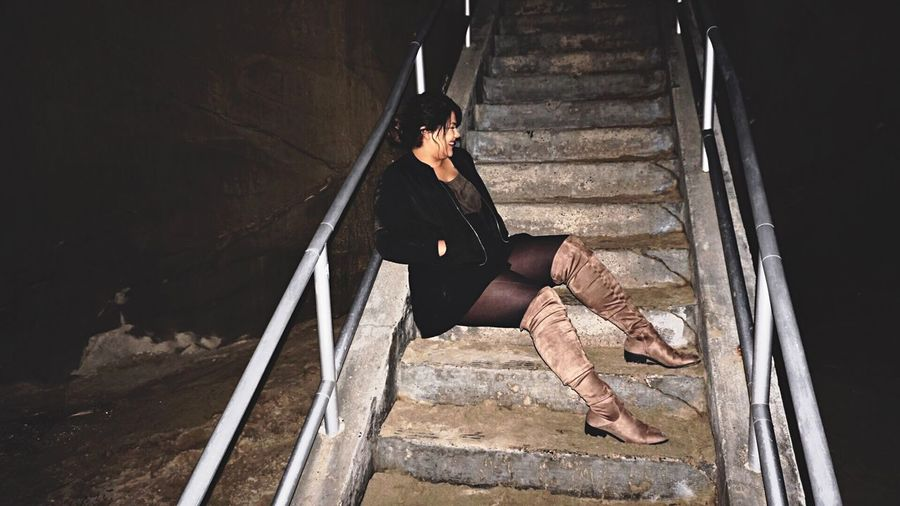 Full length of smiling young woman sitting on stairs at night
