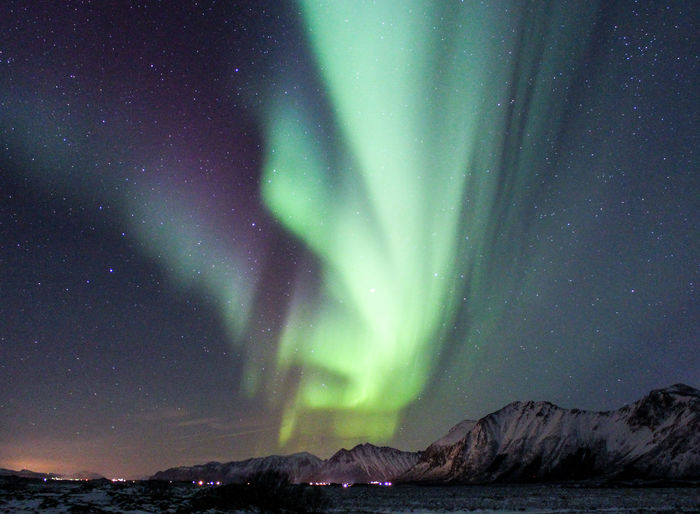 Aurora polaris over mountains against sky