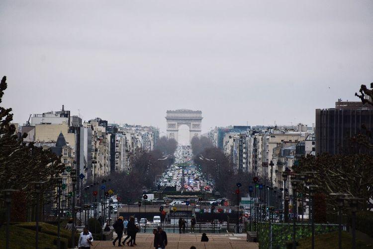 Distant view of Arc de Triomphe amidst buildings against sky in city