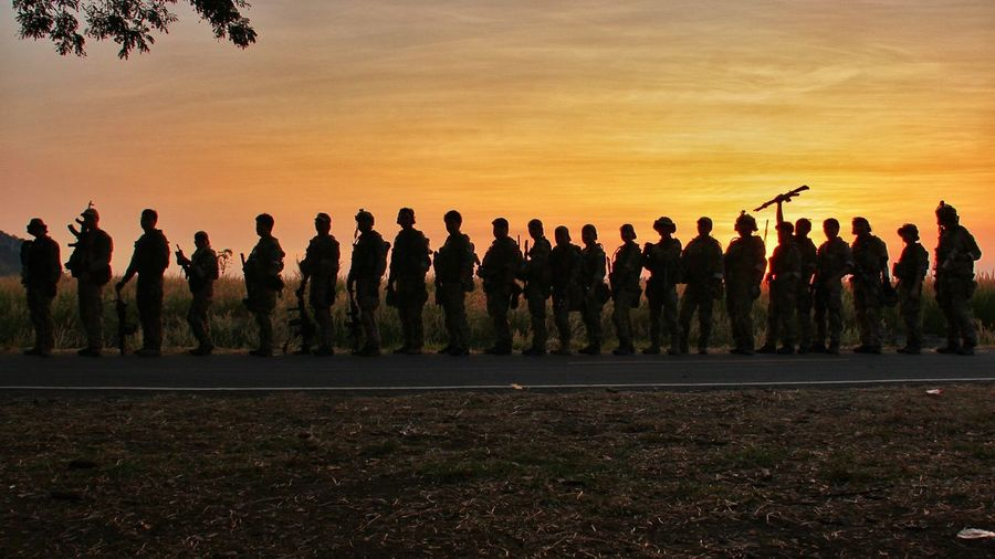 Army soldiers standing on road against sky during sunset
