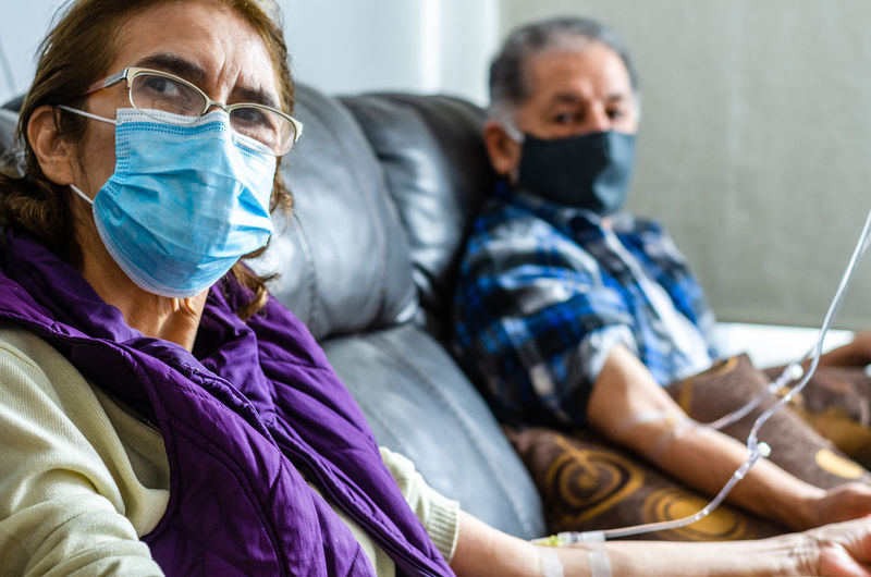 Senior couple wearing mask sitting at hospital