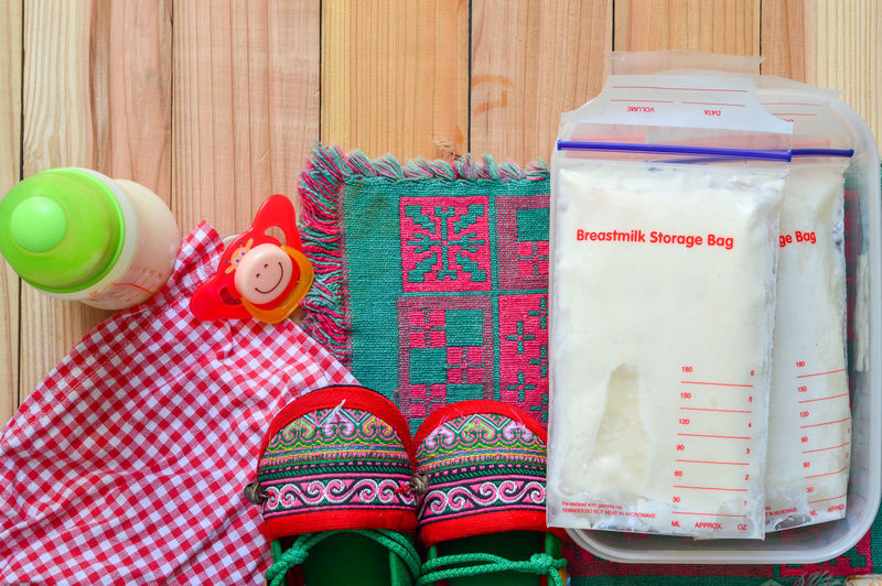 Frozen milk for baby. Indoors  One Person Multi Colored Low Section Celebration Shoe Real People Human Body Part Sock Directly Above Container Green Color Holiday Pattern Close-up Standing Floral Pattern Human Foot