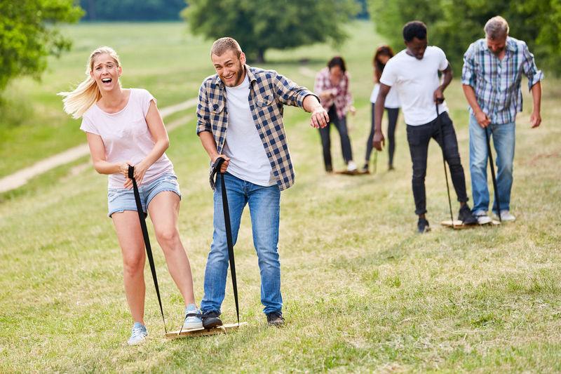 Rear view of people walking on grassland