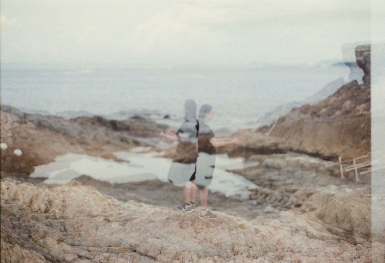 Double exposure of friends and rocky shore