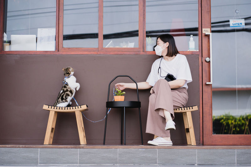 Asian woman wearing protective mask sit and play with her cat at outdoor coffee shop