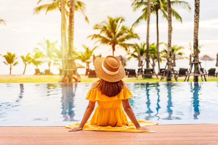 Rear view of woman wearing hat standing by swimming pool