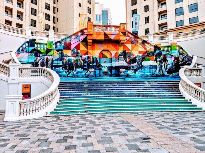 People in swimming pool against buildings in city