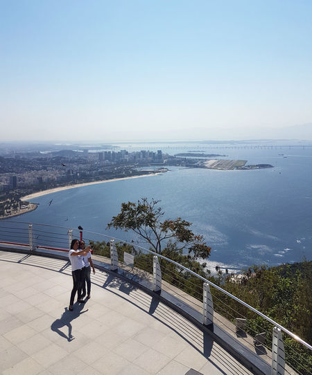 Architecture Beauty In Nature Cityscape Clear Sky Day Full Length High Angle View Leisure Activity Lifestyles Light And Shadow Looking At View Men Nature One Person Outdoors Promenade Railing Real People Scenics - Nature Sea Selfie Shadow Sky Sunlight Water
