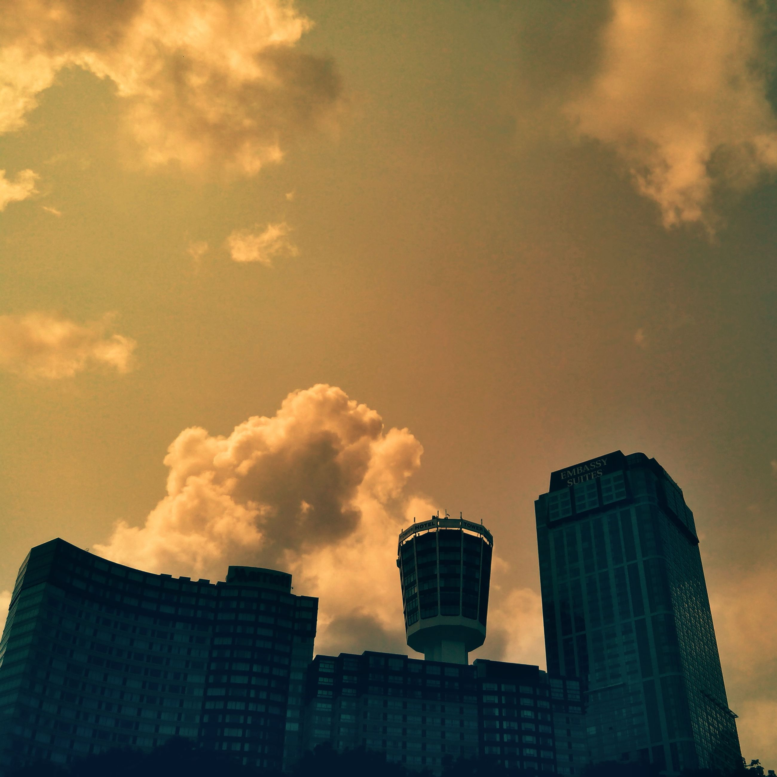 architecture, building exterior, built structure, low angle view, sky, city, cloud - sky, modern, skyscraper, tower, tall - high, office building, building, sunset, cloud, cloudy, outdoors, no people, high section, silhouette
