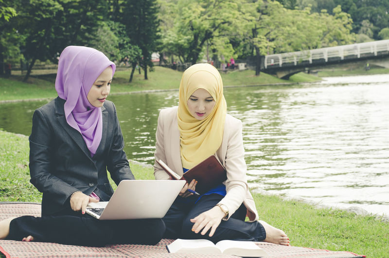Portrait of young lovely pleasant mix ethnic woman sitting on grass at summer green park and having a discussion.student and urban lifestyle Adult Computer Connection Day Headscarf Hijab Lake Laptop Nature Outdoors People Plant Real People Sitting Two People Using Laptop Water Wireless Technology Women Young Adult Young Women