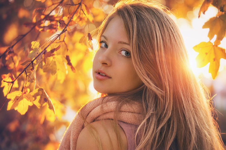 Close-up portrait of beautiful young woman during autumn