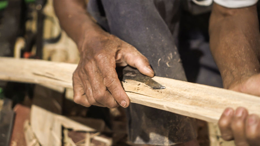 Midsection of man working on wood
