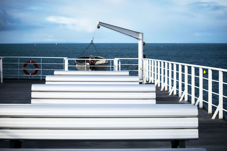 Empty seats on nautical vessel at sea against sky