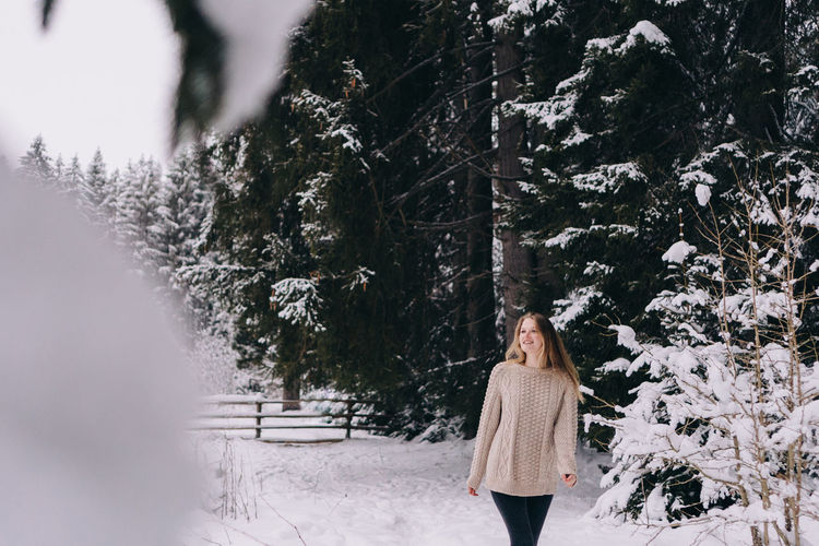 Rear view of woman standing on snow covered trees