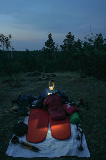caucasian female hiker reading book/writing journal at night while wildcamping, strong light from headlamp Backpacking Camping Headlamp Hiking Light Reading Travel Trekking Woman Writing Adventure Beam Book Caucasian Evening Female Hobby Journal Night Outdoors People person Sleeping Sleeping Bag