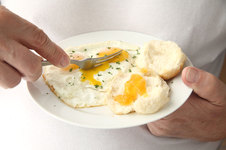 A man eating his breakfast eggs with biscuits and apricot jam. Apricot Jam Biscuits Breakfast Closeup Cutting Eating Egg Whites Egg Yolks Fingers Food Fried Eggs Front View Hands Indoors  Man Mature Person Meal Nutrition Plate Ready-to-eat Senior Sunny-side Up Unrecognizable Person