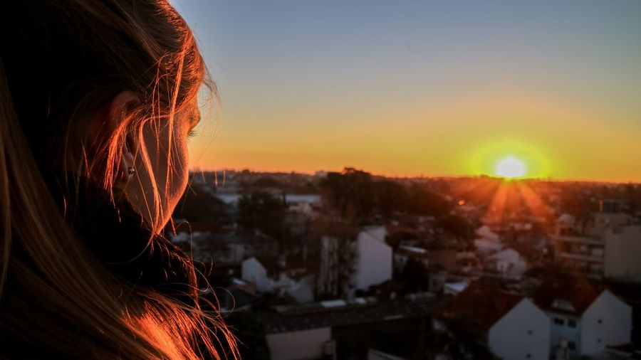 One Person Sunset Headshot Sky Portrait Sunlight Building Exterior Architecture Lifestyles Sun Adult Real People Built Structure Hair Nature Hairstyle Orange Color Leisure Activity Lens Flare Women Cityscape Outdoors Human Hair Looking At View