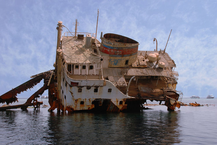 Abandoned ship in water against sky