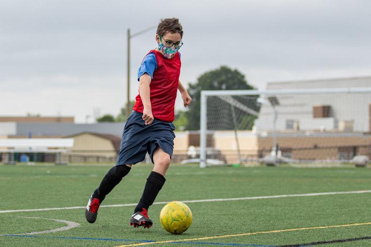 Full length of boy running on soccer field wearing face mask