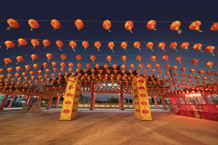 Illuminated lanterns hanging in row against orange sky