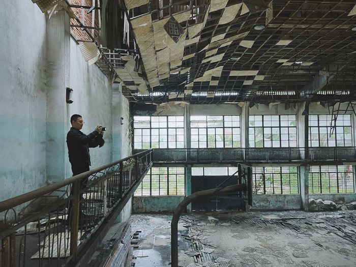 Man standing on railing of abandoned building