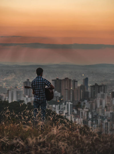 Rear view of man playing guitar while standing against cityscape and sky during sunset