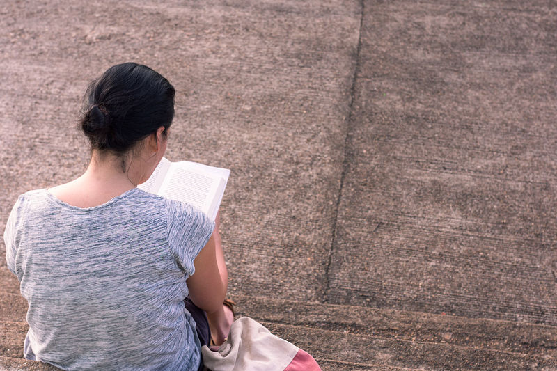 Woman reading book while sitting on steps