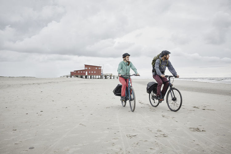 People riding bicycle on beach against sky