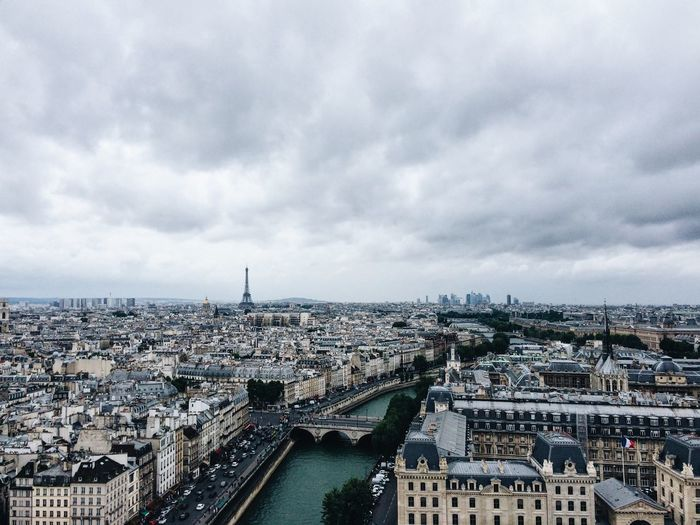 Cityscape With Eiffel Tower In Background Against Cloudy Sky