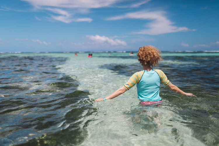 Rear view of woman in sea against sky