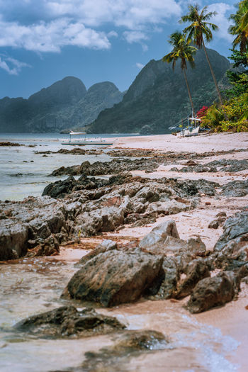 Scenic view of rocks at beach against sky