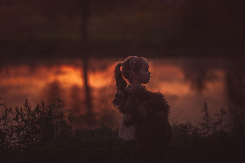 Girl with cat looking away while sitting on grass during sunset
