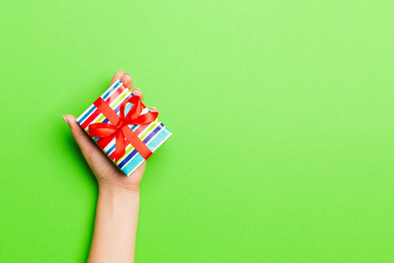 Cropped hand holding christmas present on colored background