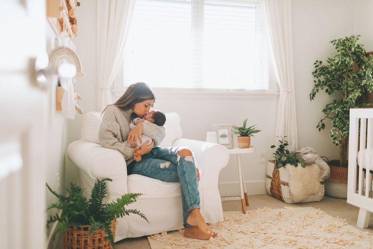 Full length of mother embracing baby while sitting on sofa at home