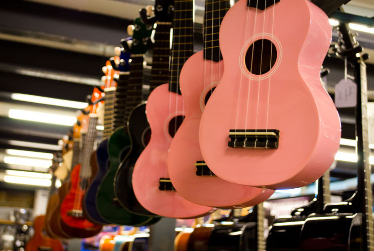 Low Angle View Of Guitars Hanging At Music Store