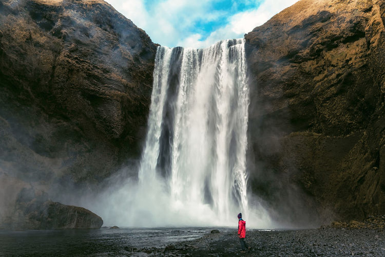 A man stands in front of the Skogafoss waterfall in South West Iceland Adventure Club Iceland Matthias Church OneMan Adventure Beauty In Nature Cliff Iceland_collection Long Exposure Low Angle View Motion Nature One Person Outdoors People Power In Nature Rock - Object Scenics Skogafoss Sky Snapshopped Travel Destinations Water Waterfall Waterfront