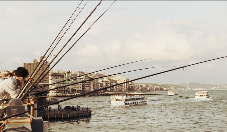 People with fishing rod by sea against sky in city